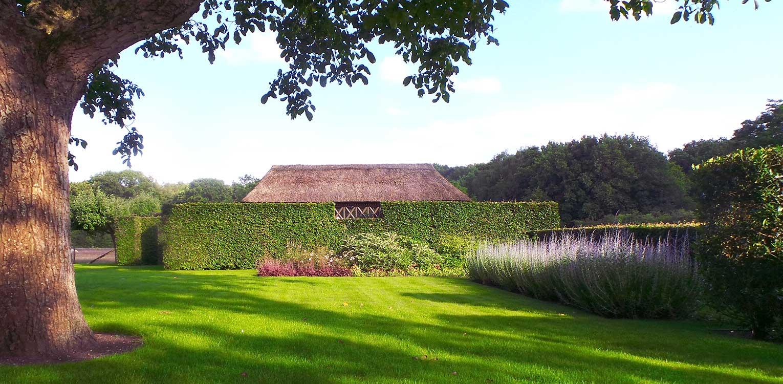 hagen om zwembad bij boerderijtuin Gorssel. De tuin valt op door zijn sterke concept, eenvoudige vormentaal en mooie verbinding met het bestaande landschap - Denkers in Tuinen.