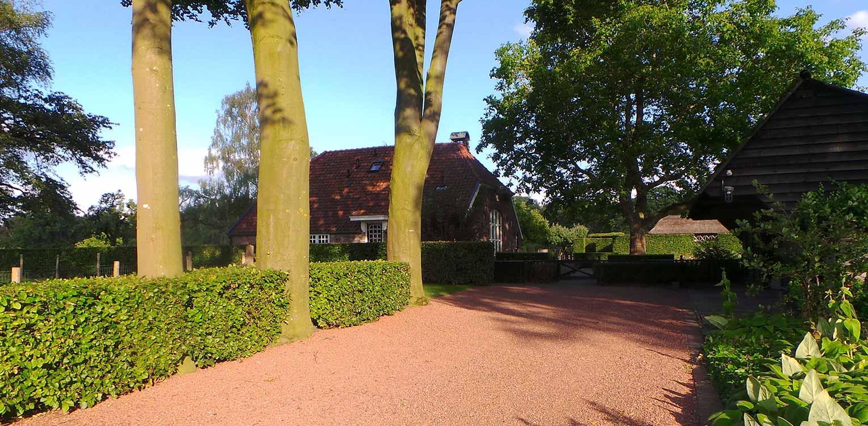inrit in halfverharding bij boerderijtuin Gorssel. De tuin valt op door zijn sterke concept, eenvoudige vormentaal en mooie verbinding met het bestaande landschap - Denkers in Tuinen.