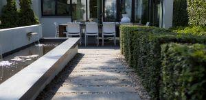 verhoogde vijver met meerdere waterlopen en taxusblokken in villatuin Bussum met formeel vormgegeven entreezijde. Het ontwerp van de achtertuin sluit naadloos aan bij nieuwe, moderne glazen uitbouw Denkers in Tuinen.