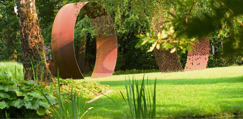 kuntwerken corten staal in kantoortuin Apeldoorn. De stijlvolle nieuwe tuinaanleg herstelde de oorspronkelijke verbinding met het tegenover gelegen Oranjepark weer Denkers in Tuinen.
