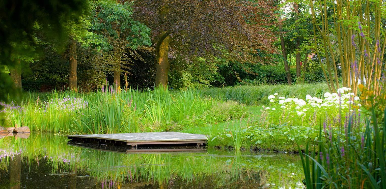vlonder in kantoortuin Apeldoorn. De stijlvolle nieuwe tuinaanleg herstelde de oorspronkelijke verbinding met het tegenover gelegen Oranjepark weer Denkers in Tuinen.