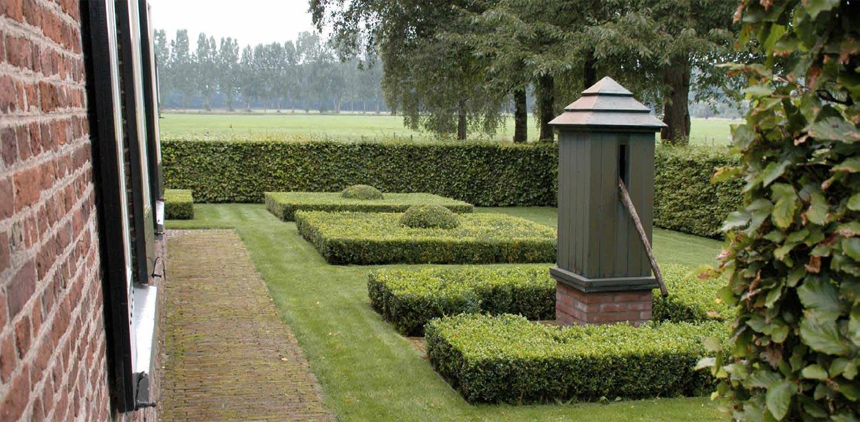 waterpomp opgenomen in vormgesnoeide buxusblokken boerderijtuin Gorssel. De tuin valt op door zijn sterke concept, eenvoudige vormentaal en mooie verbinding met het bestaande landschap - Denkers in Tuinen.