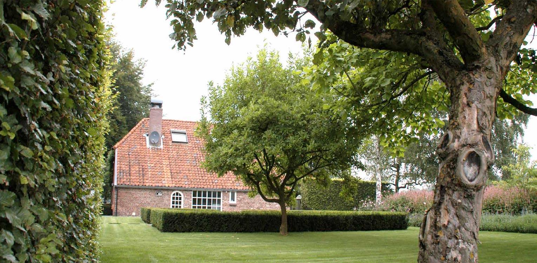 met taxus blokhaag omzoomd verdiept terras boerderijtuin Gorssel. De tuin valt op door zijn sterke concept, eenvoudige vormentaal en mooie verbinding met het bestaande landschap - Denkers in Tuinen.