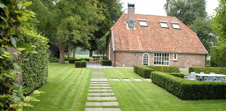 met taxus blokhaag omzoomd verdiepte terras met pad staptegels in gras boerderijtuin Gorssel. De tuin valt op door zijn sterke concept, eenvoudige vormentaal en mooie verbinding met het bestaande landschap - Denkers in Tuinen.