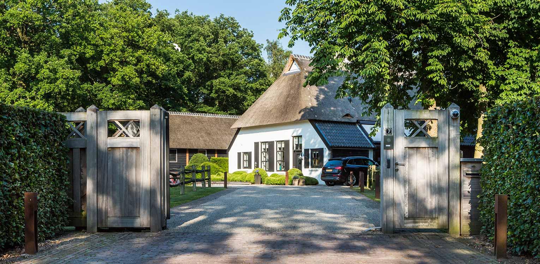 entreepoort boerderijtuin Nijverdal. Er is eenheid en stijl in de aanwezige verrommeling gebracht en kunnen de pony's rondom tot aan de woning komen Denkers in Tuinen.