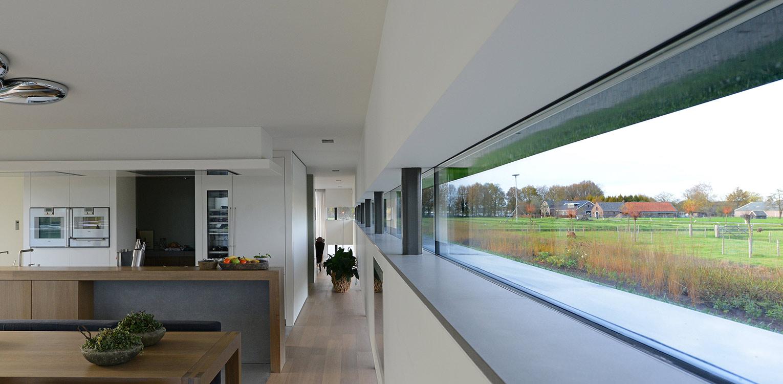 Moderne villatuin in buitengebied. Essentieel voor het ontwerp van deze tuin is de lengtebeleving. Het graslandschap wordt zelfs letterlijk onder het huis doorgetrokken!
