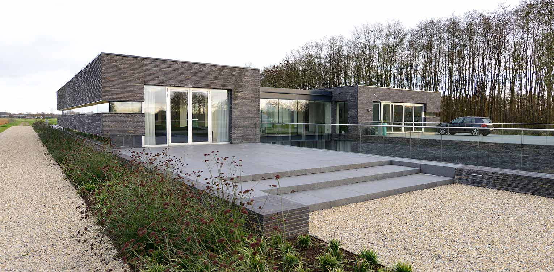 Moderne villatuin met natuursteen terras. Essentieel voor het ontwerp van deze tuin is de lengtebeleving. Het graslandschap wordt zelfs letterlijk onder het huis doorgetrokken!