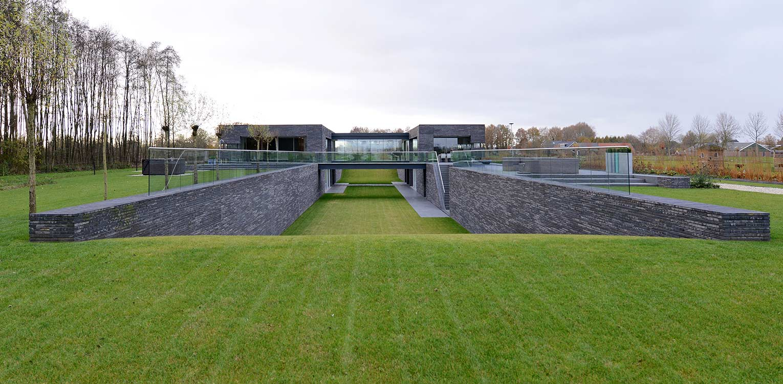 Moderne villatuin met verdiept grasdak en knotwilgen. Essentieel voor het ontwerp van deze tuin is de lengtebeleving. Het graslandschap wordt zelfs letterlijk onder het huis doorgetrokken!