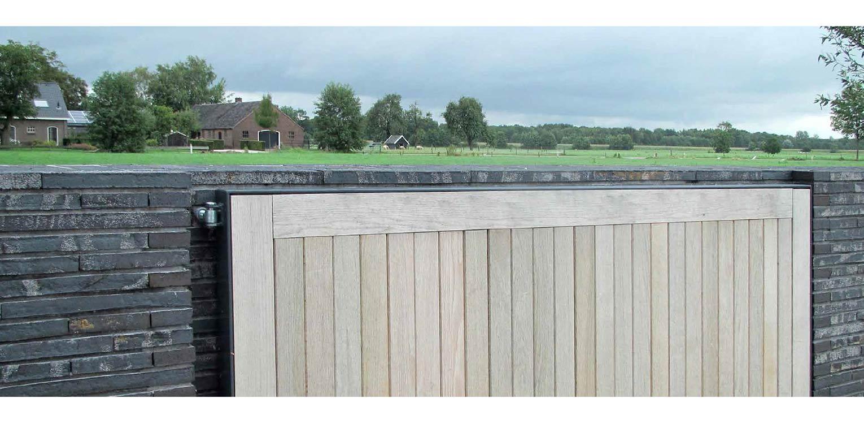 Moderne villatuin met entreepoort. Essentieel voor het ontwerp van deze tuin is de lengtebeleving. Het graslandschap wordt zelfs letterlijk onder het huis doorgetrokken!