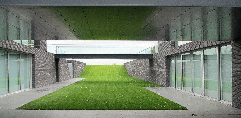 Moderne villatuin met verdiept grasdak. Essentieel voor het ontwerp van deze tuin is de lengtebeleving. Het graslandschap wordt zelfs letterlijk onder het huis doorgetrokken!