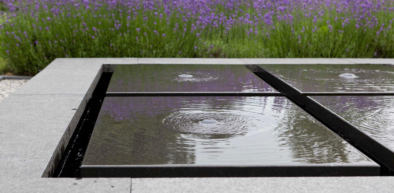 detail waterelement in natuursteen villatuin Dronten. Tuin aan de polderrand van Dronten, gekoppeld aan het omliggende polderlandschap met noodzakelijke windbeschutting - Denkers in Tuinen