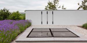 waterelement voor witte tuinmuur met inbouw verlichting villatuin Dronten. Tuin aan de polderrand van Dronten, gekoppeld aan het omliggende polderlandschap met noodzakelijke windbeschutting - Denkers in Tuinen