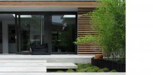 bamboe en betonterras patiotuin Diepenveen. Het in de woning toegepaste beton is consequent in de buitenruimte doorgetrokken - mede als podium voor kunst - Denkers in Tuinen