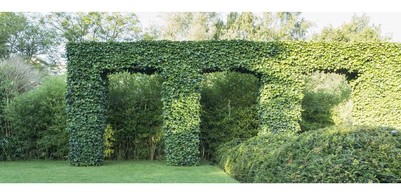 bogen met klimop en taxuswolk in villatuin Naarden. In het strakke en moderne tuinontwerp zijn enkele niet alledaagse grote 'spannende' lijnen en elementen opgenomen - Denkers in tuinen.