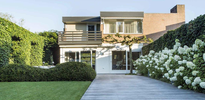 vlonderterras met hortensia's en taxuswolk in villatuin Naarden. In het strakke en moderne tuinontwerp zijn enkele niet alledaagse grote 'spannende' lijnen en elementen opgenomen - Denkers in tuinen.