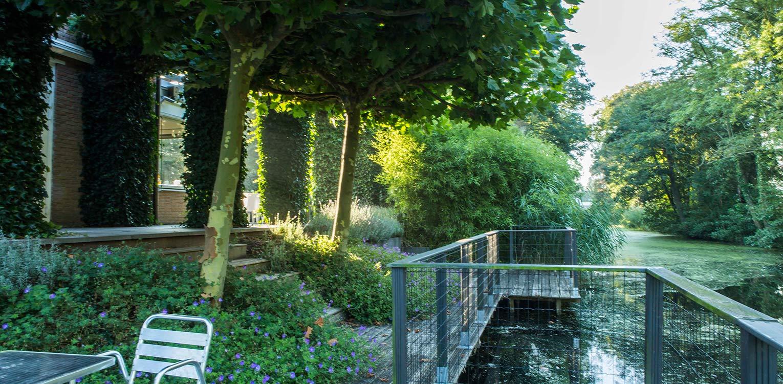 verdiept vlonder tuindeel villatuin Naarden. In het strakke en moderne tuinontwerp zijn enkele niet alledaagse grote 'spannende' lijnen en elementen opgenomen - Denkers in tuinen.