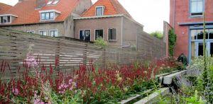 treilage stadstuin Willemstad aan de historische haven. Het monumentale karakter van de woning is teruggebracht in de natuurstenen waterloop. denkers in Tuinen.