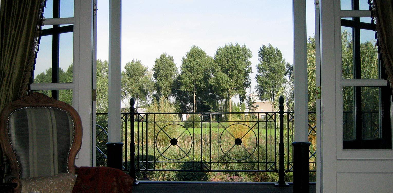 zicht op de landschappelijke tuin Sloten vanuit de zitkamer waar de sfeer van het achterliggend natuurpark tot ver in de tuin voelbaar is naast veel bloemrijke borders Denkers in Tuinen.