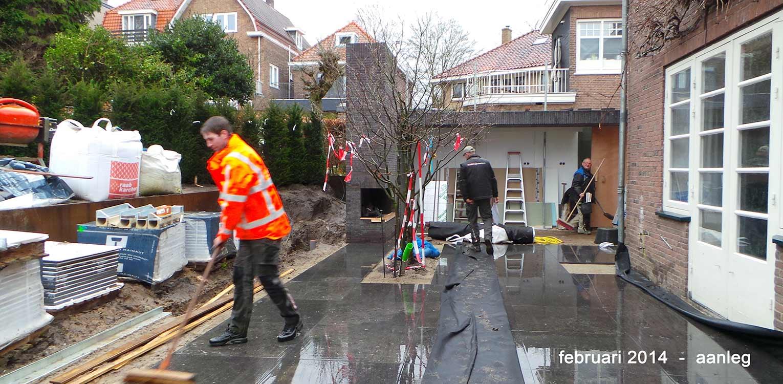 aanleg terras in natuursteen stadstuin Arnhem waar op korte afstand fors hoogteverschil wordt overwonnen o.m. door aanleg van zware blokhaag tegen stalen keerwand - Denkers in Tuinen