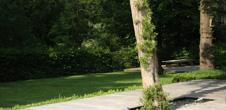 villatuin Apeldoorn waar grote vlonderterrassen en vrij in het gras staande bomen op de grens van het Matenpark de sfeer bepalen Denkers in Tuinen
