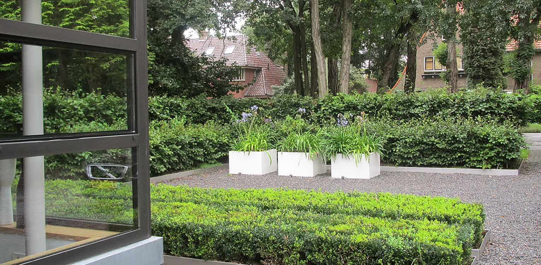 stadstuin Zeist waar minimalisme uitgangspunt is voor het tuinontwerp. Grind- en groene vlakken, identieke plantenbakken en groene hagen ronden af Denkers in Tuinen.
