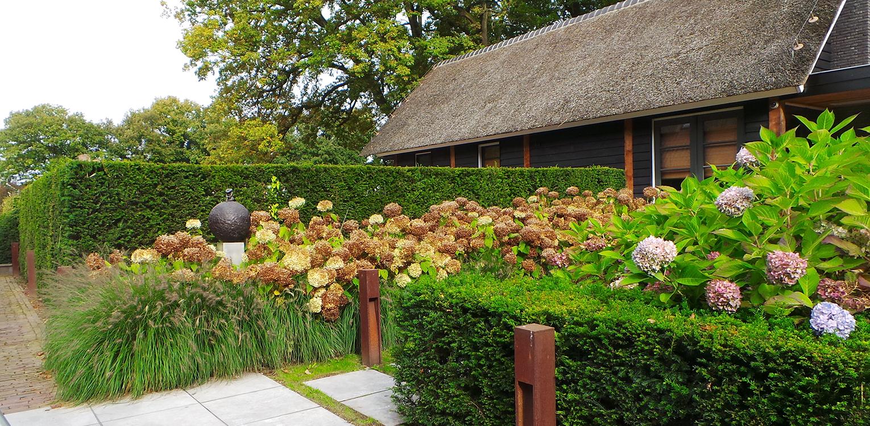 Wellness bij boerderijtuin Nijverdal. Er is eenheid en stijl in de aanwezige verrommeling gebracht en kunnen de pony's rondom tot aan de woning komen Denkers in Tuinen.