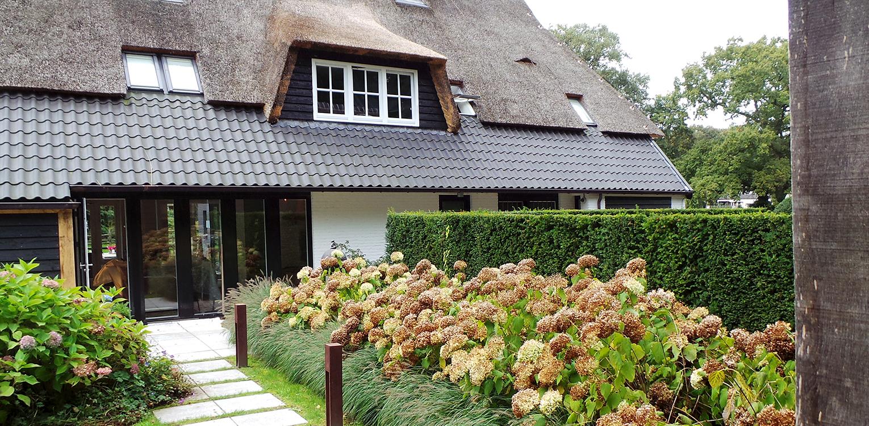 Hydrangea 'Annabelle' in boerderijtuin Nijverdal. Er is eenheid en stijl in de aanwezige verrommeling gebracht en kunnen de pony's rondom tot aan de woning komen Denkers in Tuinen.