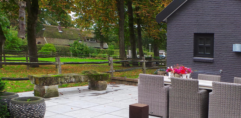 Natuursteen terras boerderijtuin Nijverdal. Er is eenheid en stijl in de aanwezige verrommeling gebracht en kunnen de pony's rondom tot aan de woning komen Denkers in Tuinen.